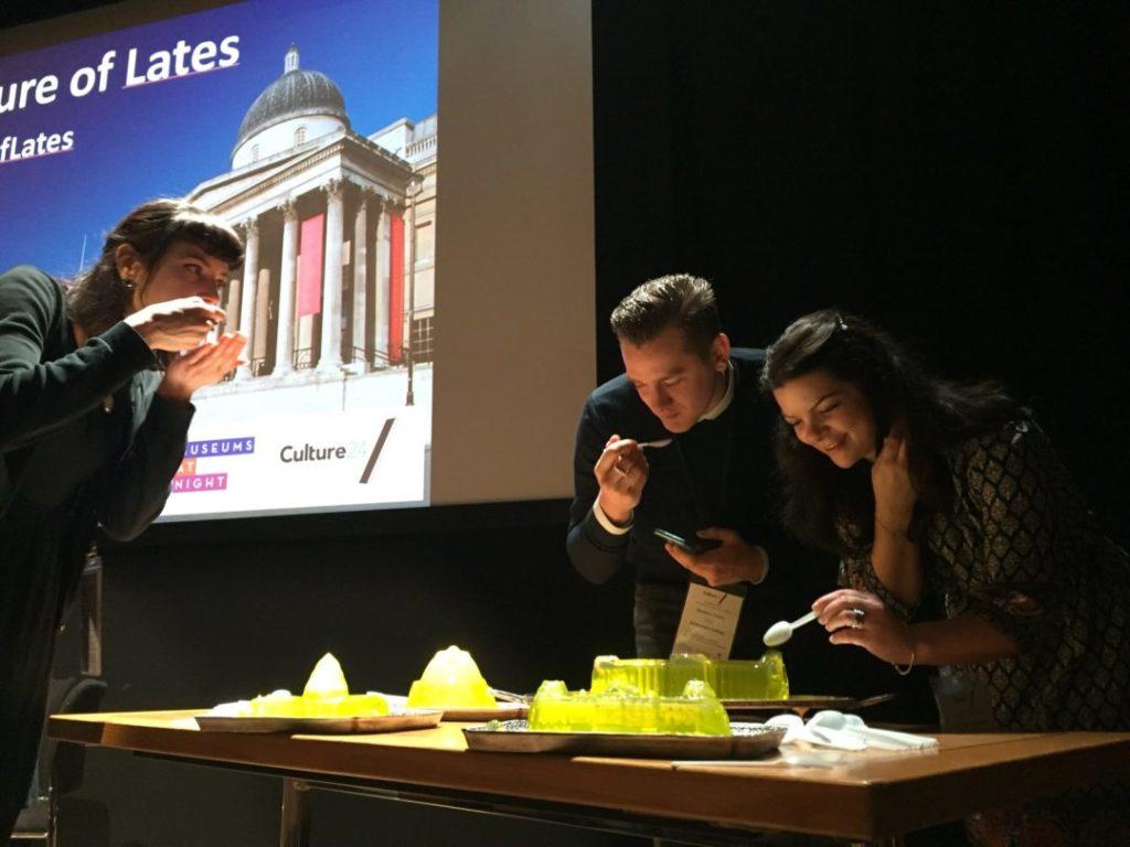 People with spoons sampling luminous jellies shaped like buildings