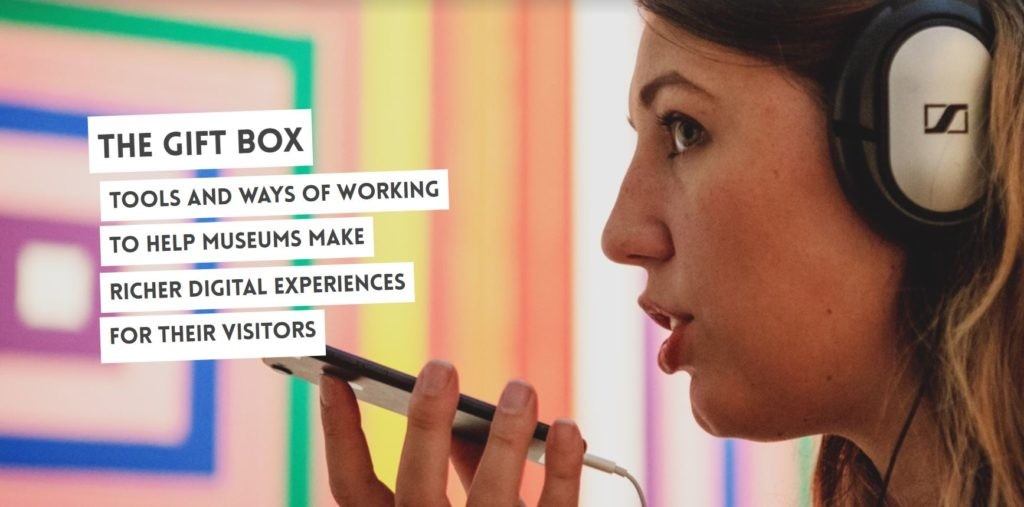 A girl wearing headphones in a gallery talking into a mobile phone, with the words GIFT BOX