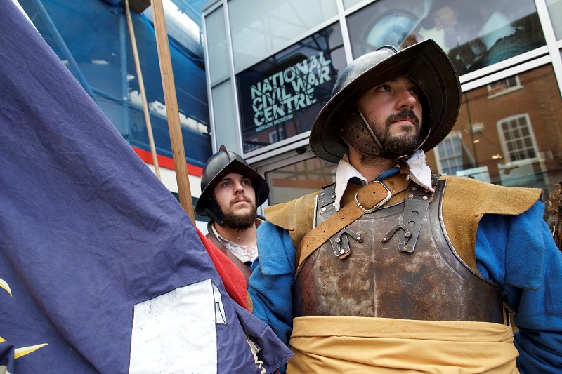 Two guards dressed in English Civil War uniforms holding a blue flag outside the National Civil War Centre