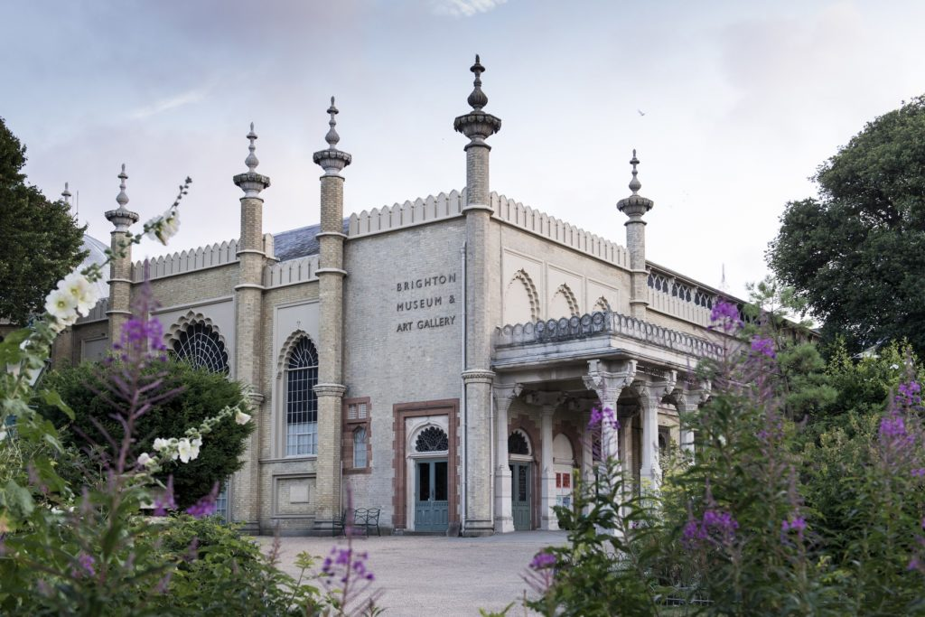 Brighton Museum and Art Gallery building with purple flowers in the foreground and pale blue sky