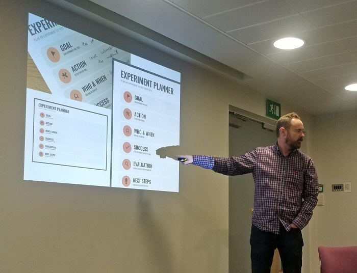 A man pointing at the word SUCCESS in a presentation