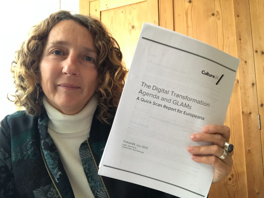a woman with curly hair holding a printed report