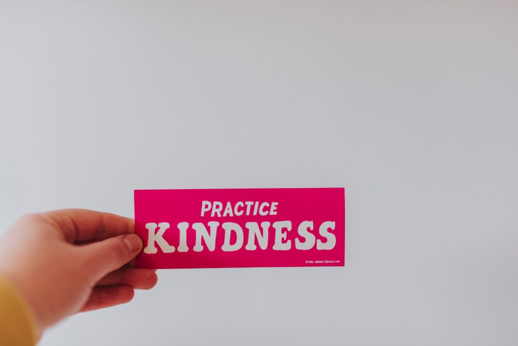 a hand holding a card with the words PRACTICE KINDNESS on