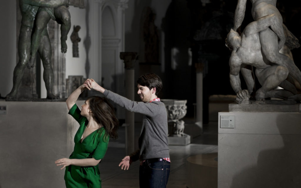 A couple dancing in a sculpture gallery at night